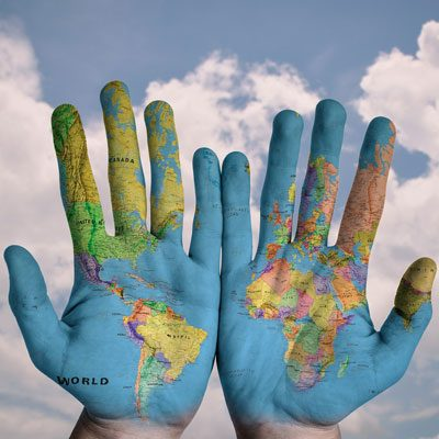 [Image description: Photograph of a pair of hands held up. A picture of the globe is painted on the back of them.]