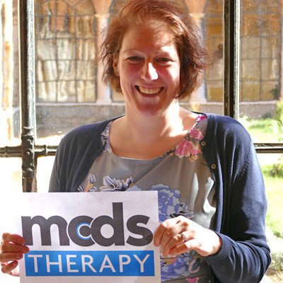 [Image description: Senior Trial Manager, Sonya, holds up a sign with the MCDS Therapy logo on it.]